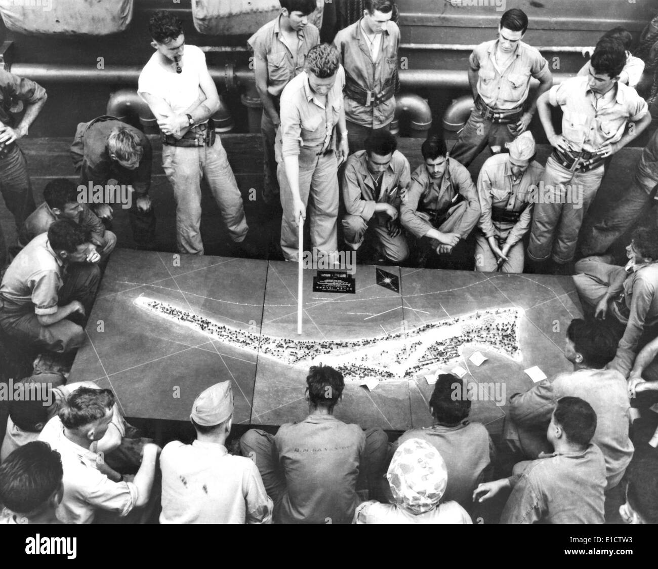 U.S. Marines study a relief model of Tarawa Atoll on a Navy transport before the battle. Ca. Nov.16-19, 1944, World War 2. - Stock Image