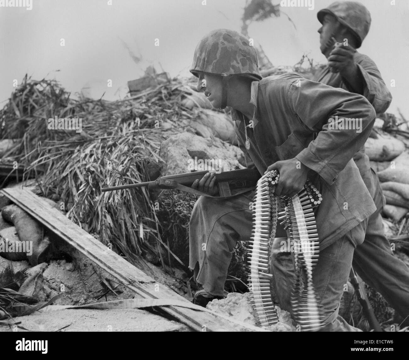 On Tarawa, a U.S. Marine, with a carbine and a bandolier of bullets. He waits for his buddy to toss a hand grenade, before he - Stock Image