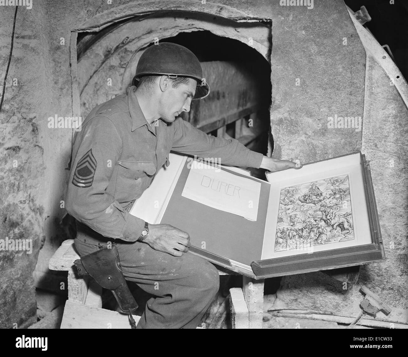 U.S. Army sergeant Harold Maus inspects a Durer engraving hidden in the Merkers salt mine. It is among artworks Stock Photo