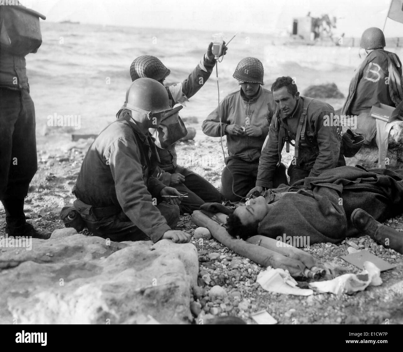 Medics administer a plasma transfusion to a wounded soldier on Omaha Beach on D-day. He is a survivor of a landing craft sunk - Stock Image