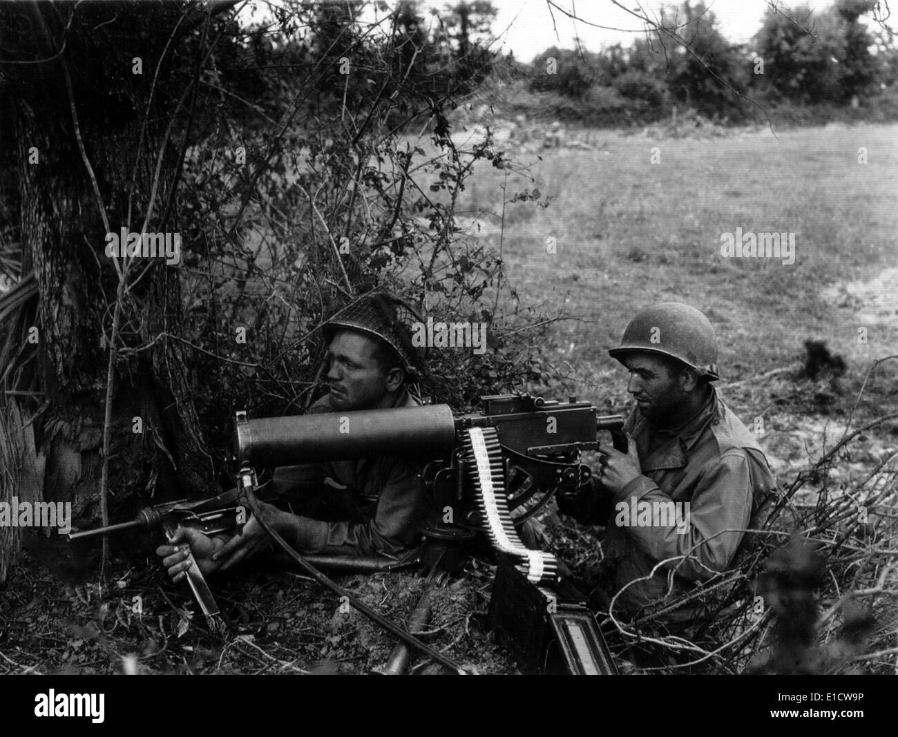 Two U.S. soldiers positioned in a Normandy hedgerow with a water-cooled Browning machine gun. The water inlet pipe Stock Photo