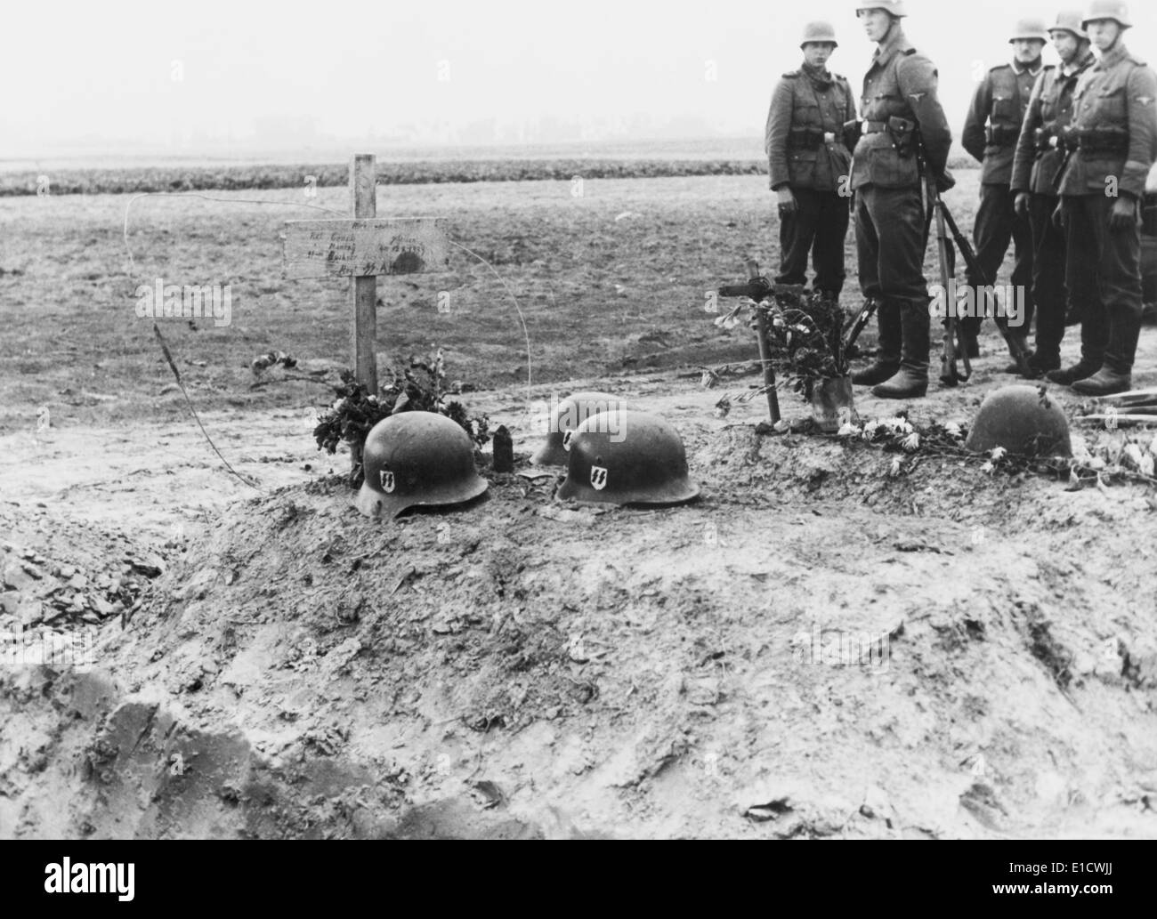German Waffen-SS troops at the helmet topped graves of their fellows during the invasion of Poland. Sept. 1939. World War 2. - Stock Image