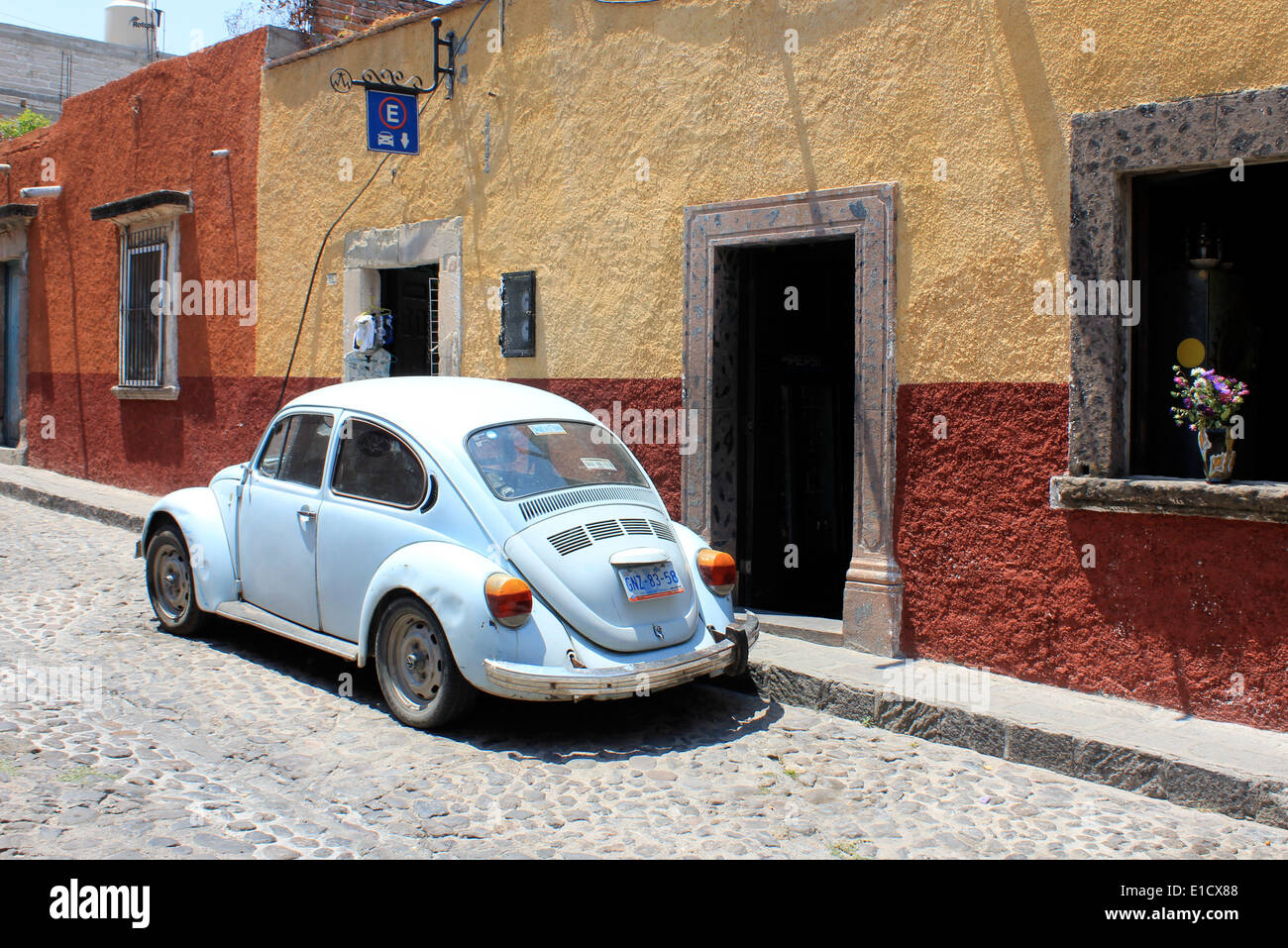 Light blue VW Beetle car outside typical colourful houses in San Miguel de Allende, Guanajuato, Mexico - Stock Image
