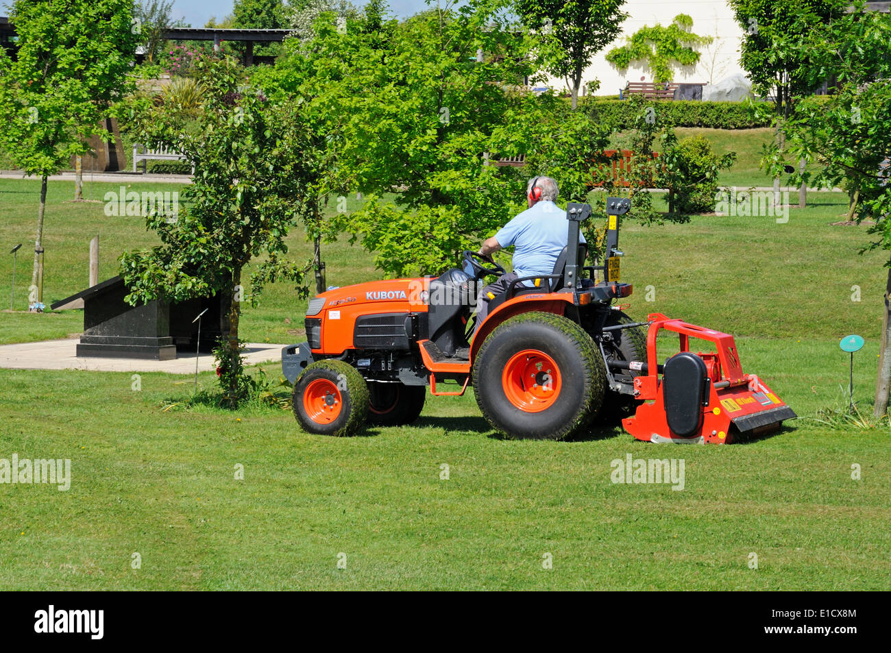 Gardener on a ride on mower mowing the lawns at the National Memorial Arboretum, Alrewas,  UK. - Stock Image