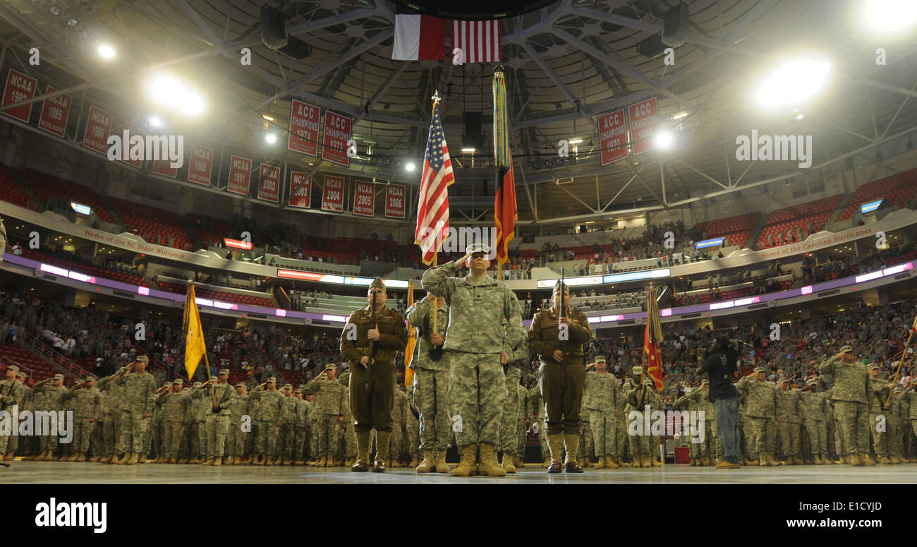 U.S. Soldiers salute during the playing of the national anthem during a homecoming ceremony at the RBC Center in Raleigh, N.C., - Stock Image