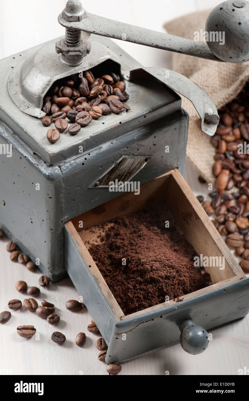 old coffee grinder with burlap and coffee beans on wooden table - Stock Image