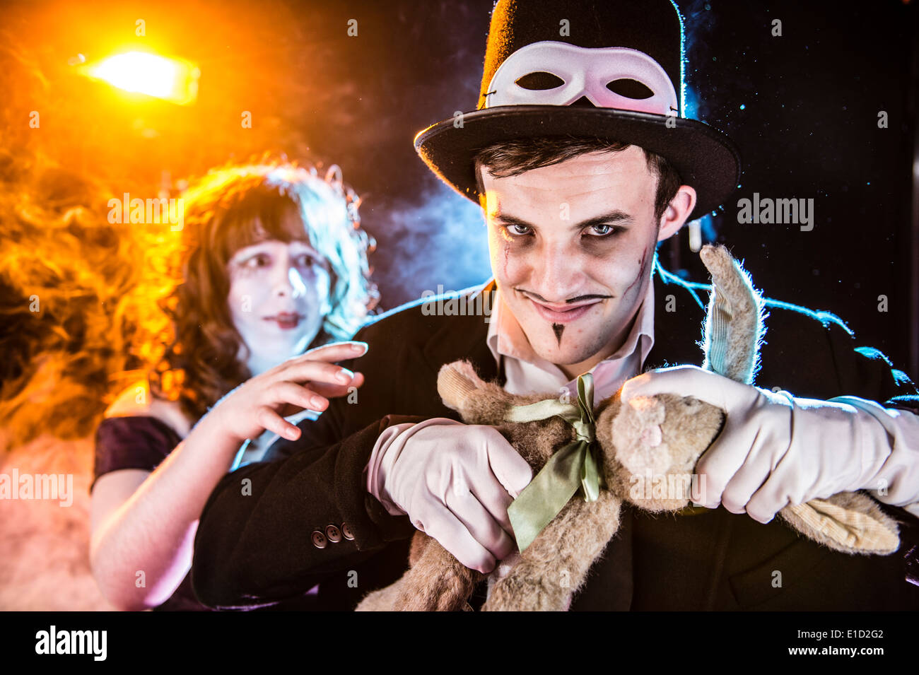 An evil smirking magician about to pull a childs soft toy rabbit's head off - Stock Image