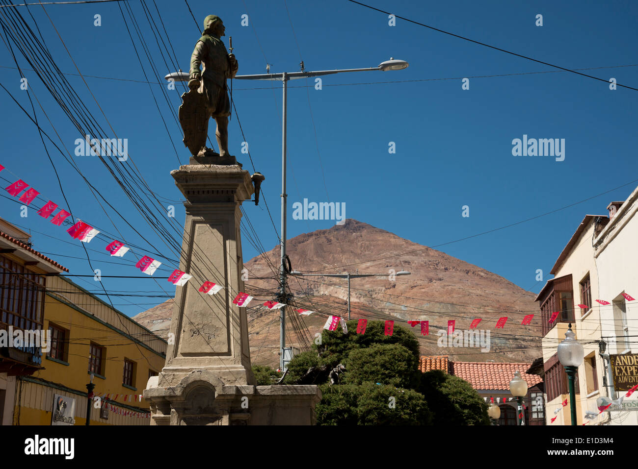 Statue in Potosi, Bolivia, with the silver mine behind it. - Stock Image