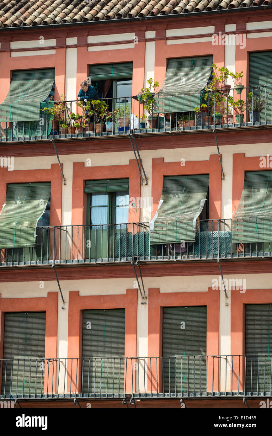 A woman surveys the square from her balcony in the Plaza de la Corredera, Cordoba, Spain. - Stock Image