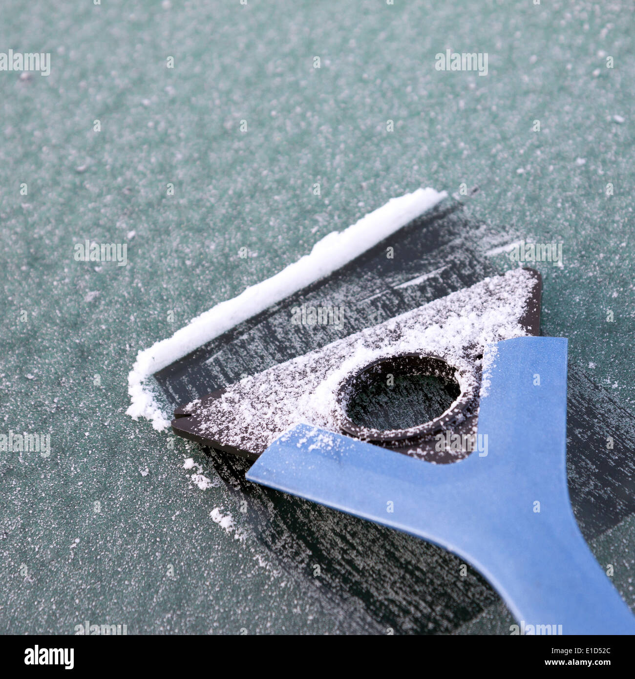 Window scraper on icy car windshield - Stock Image