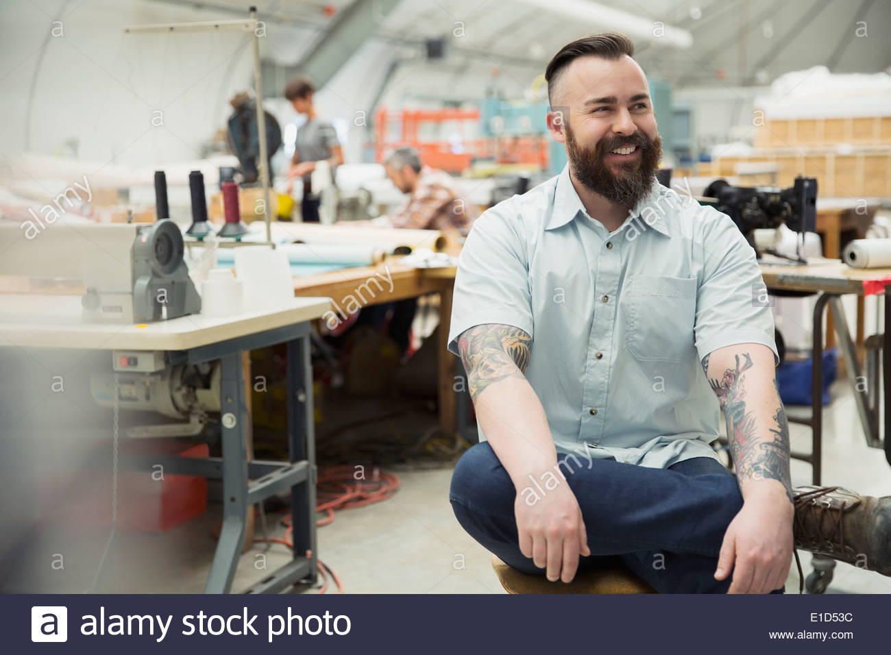 Smiling worker in textile manufacturing plant - Stock Image