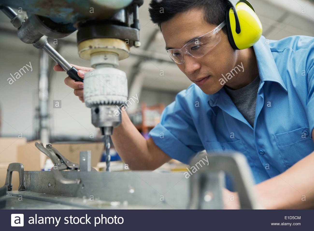 Worker operating drill machinery in manufacturing plant - Stock Image