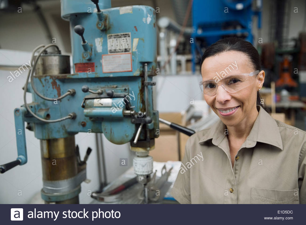 Smiling worker next to machinery in manufacturing plant - Stock Image