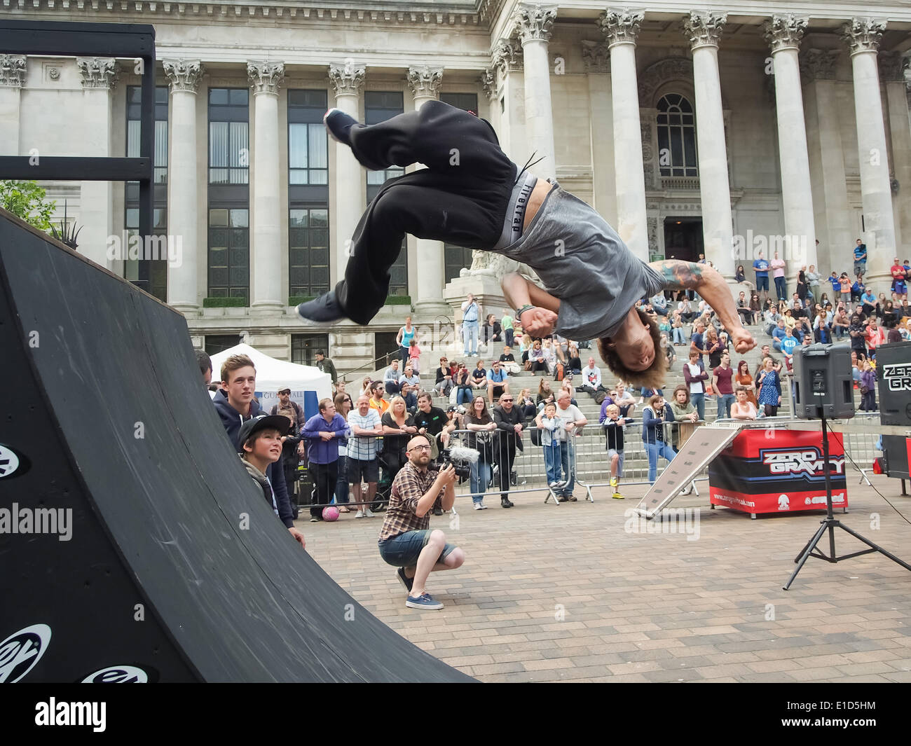 A free runner uses a quarter pipe to flip himself during the Portsmouth street games 2014 - Stock Image