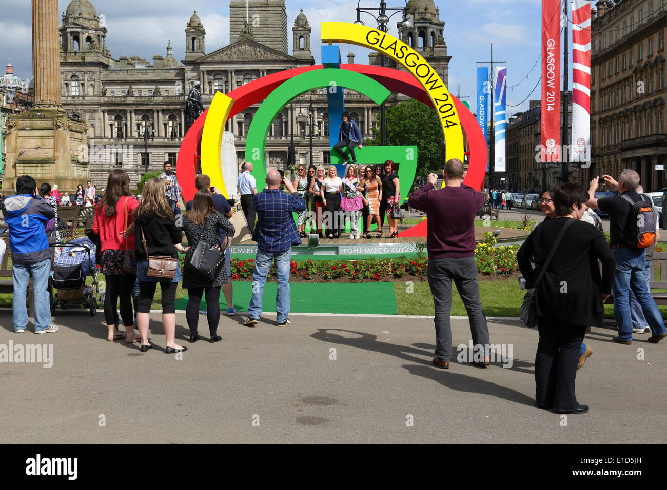Glaswegians and visitors to the city exploring the Glasgow 2014 Commonwealth Games Logo on George Square in Glasgow city centre, Scotland, UK - Stock Image