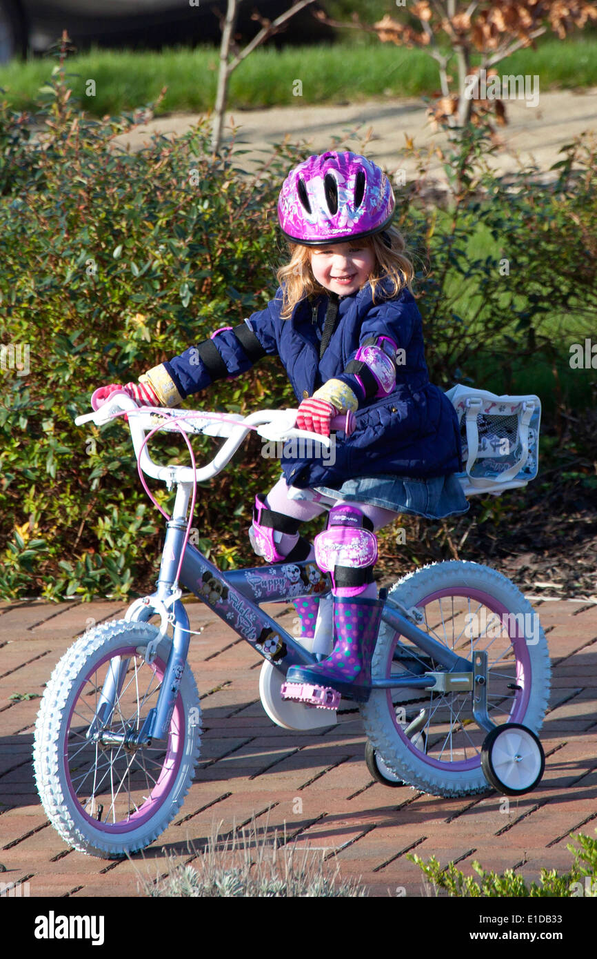 Four 4 year old girl riding her bike Stock Photo