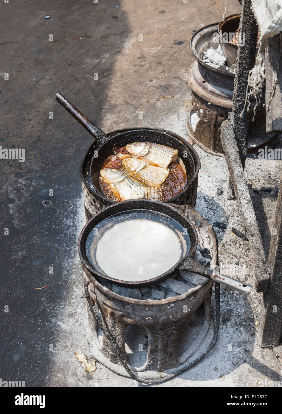 Fish heads cooking and water boiling in blackened frying pans in a charcoal brazier in Maramba Market, Livingstone, Zambia - Stock Image