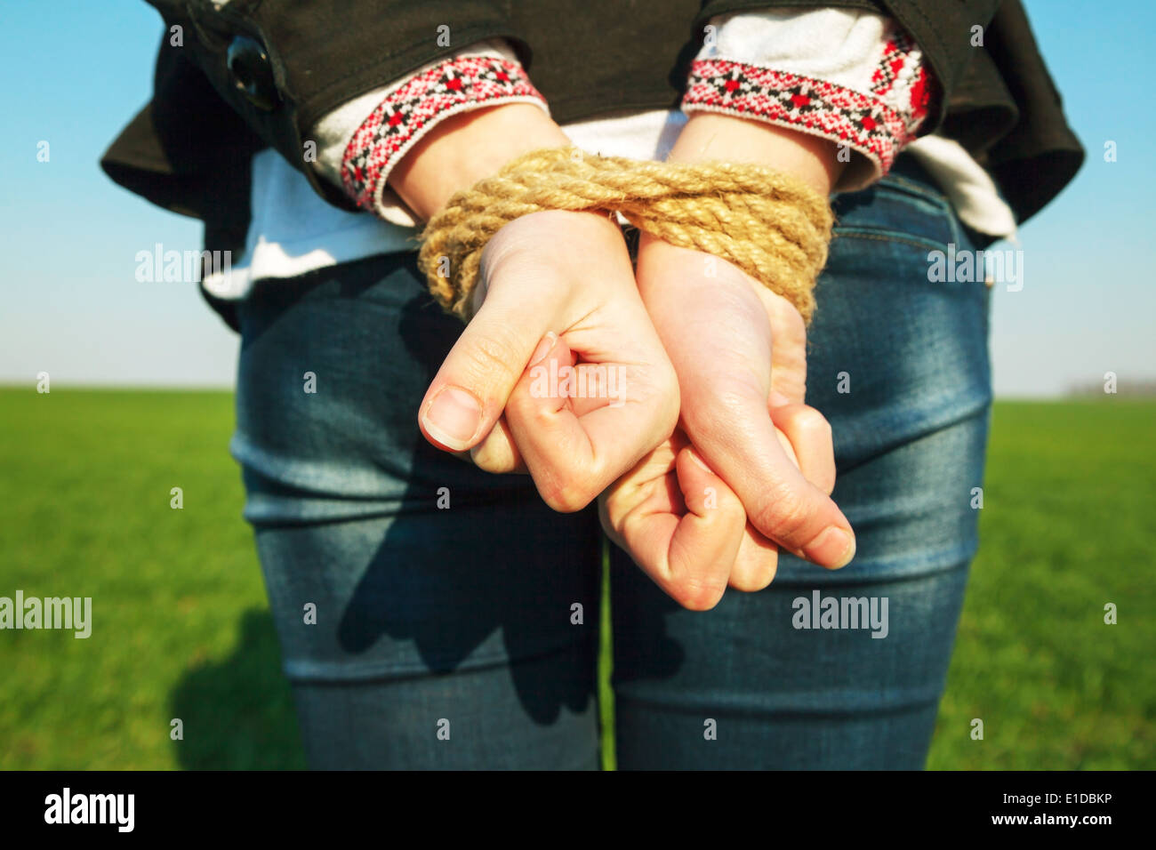Female hands tied up with the rope - Stock Image