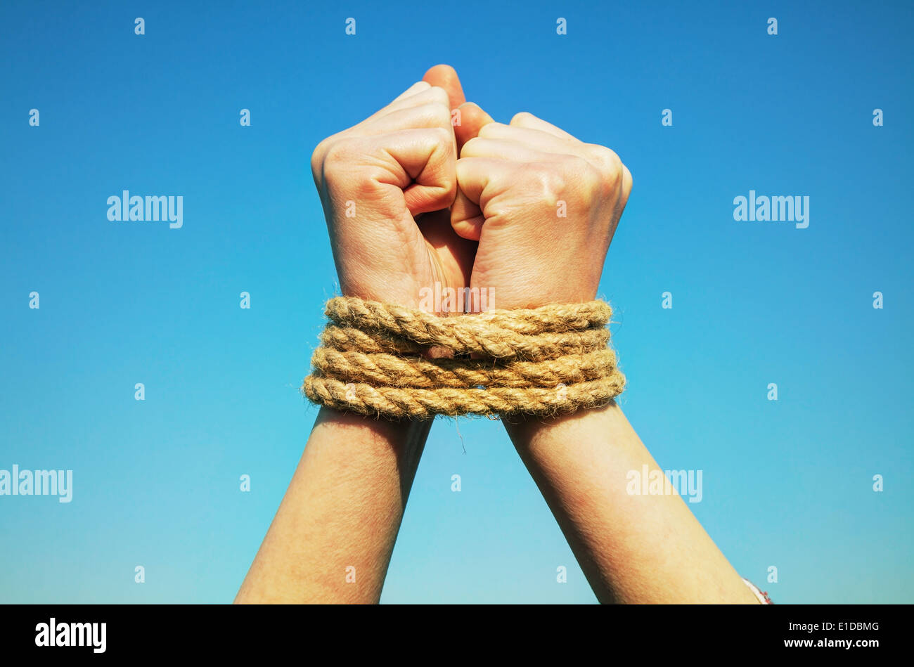 Hands tied up with rope against blue sky - Stock Image