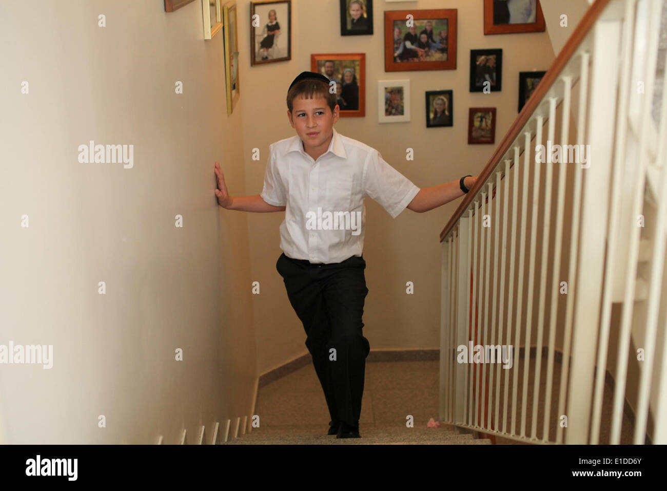 (140601) -- JERUSALEM, June 1, 2014 (Xinhua) -- Tzviel Noyman stands in front of the wall with family photos at his home in Beit Shemesh, about 20 km from Jerusalem, on May 30, 2014. Tzviel Noyman is an Israeli Ultra-Orthodox boy in a family with six children, three boys and three girls. He is ten years old this year and a grade three pupil of Torat Moshe elementary school, which is only opened to Jewish children. Tzviel has eight classes each day, including Hebrew, English, mathematics and Jewish religion, which has four classes each day including Talmud, Mishnah and Gemara. Tzviel likes the - Stock Image