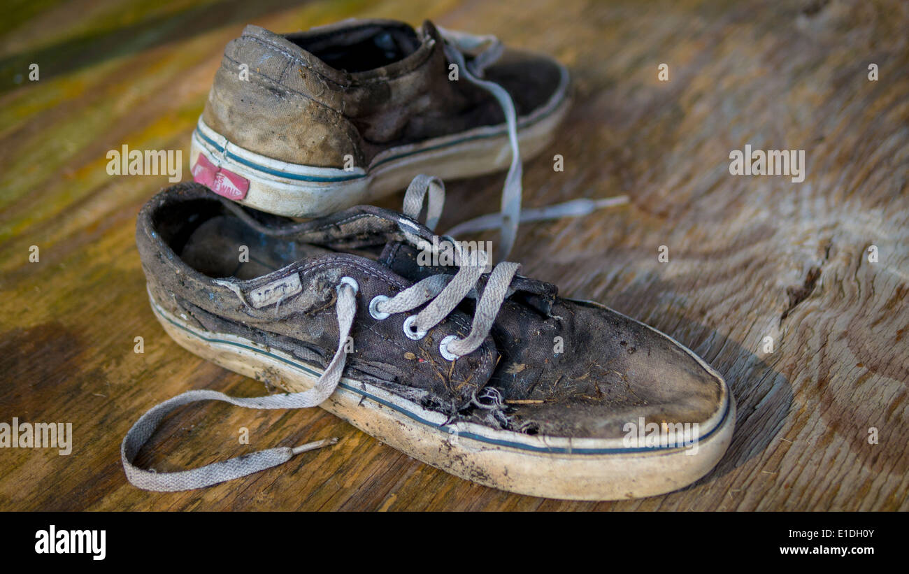 Pair of very worn Vans trainers/sneakers. - Stock Image
