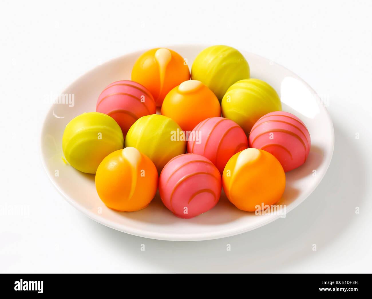 White chocolate bonbons with fruit ganache filling - Stock Image