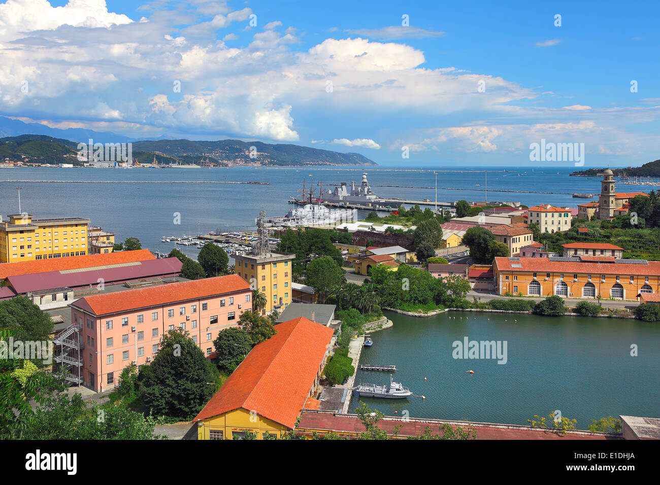 View of navy base on gulf of La Spezia under beautiful blue sky with white clouds on Mediterranean sea in Italy. - Stock Image