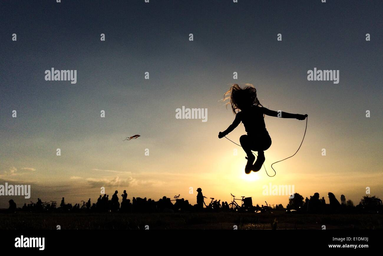 Berlin, Germany. 31st May, 2014. The silhouette of a girl jumping rope on Tempelhofer Feld in Berlin, Germany, 31 May 2014. Photo: Ole Spata/dpa/Alamy Live News - Stock Image