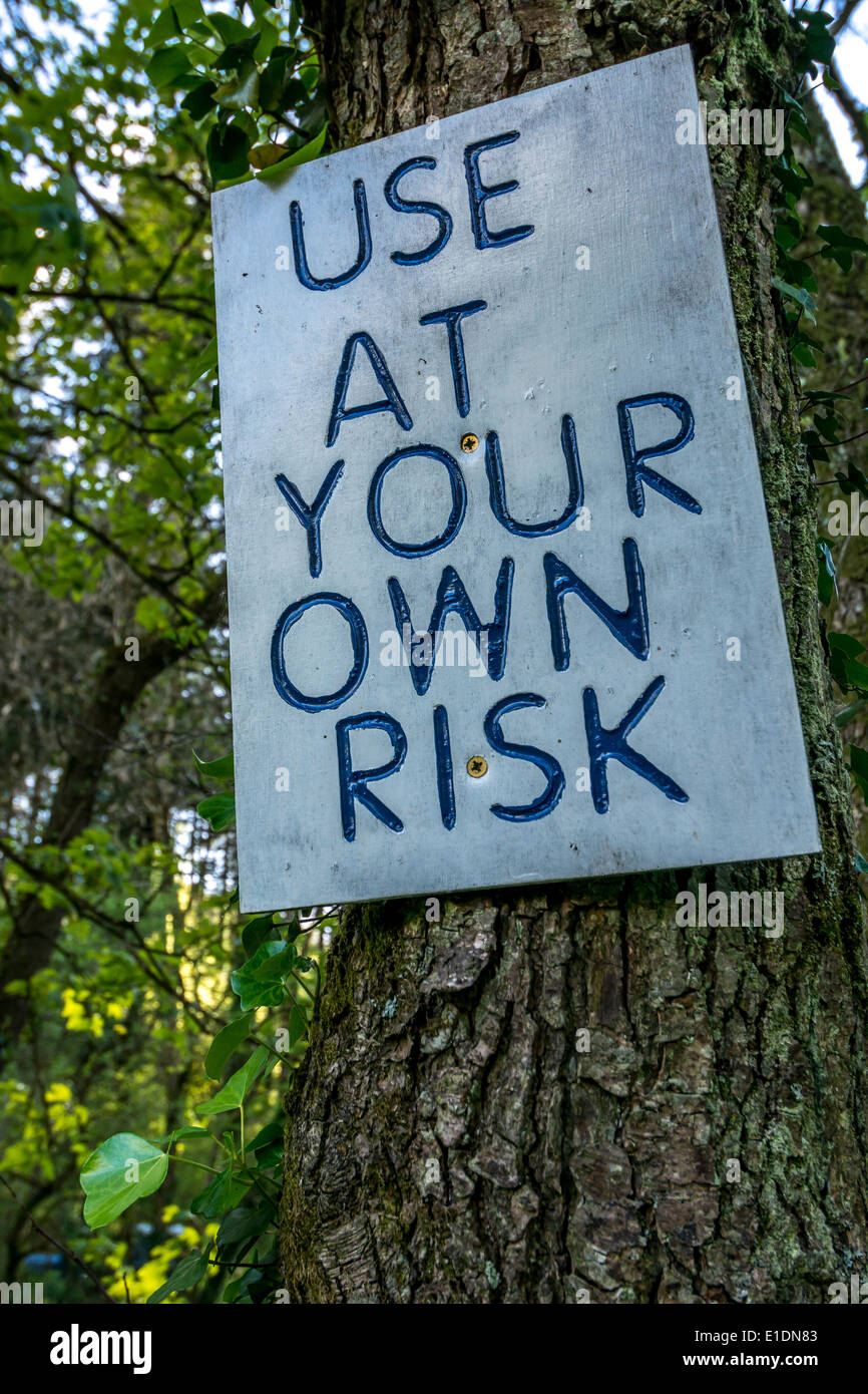 Simple notice nailed to a tree warning walkers of a hazard along a footpath. Metaphor - risk assessment, risk analysis, safety evaluation. - Stock Image