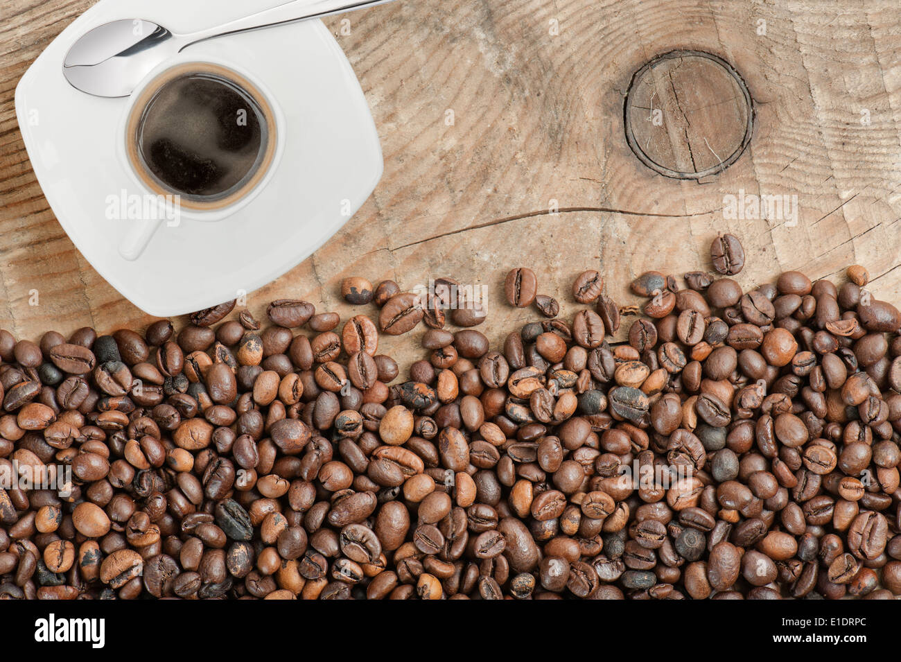coffee beans on wooden table with cup of coffee - Stock Image