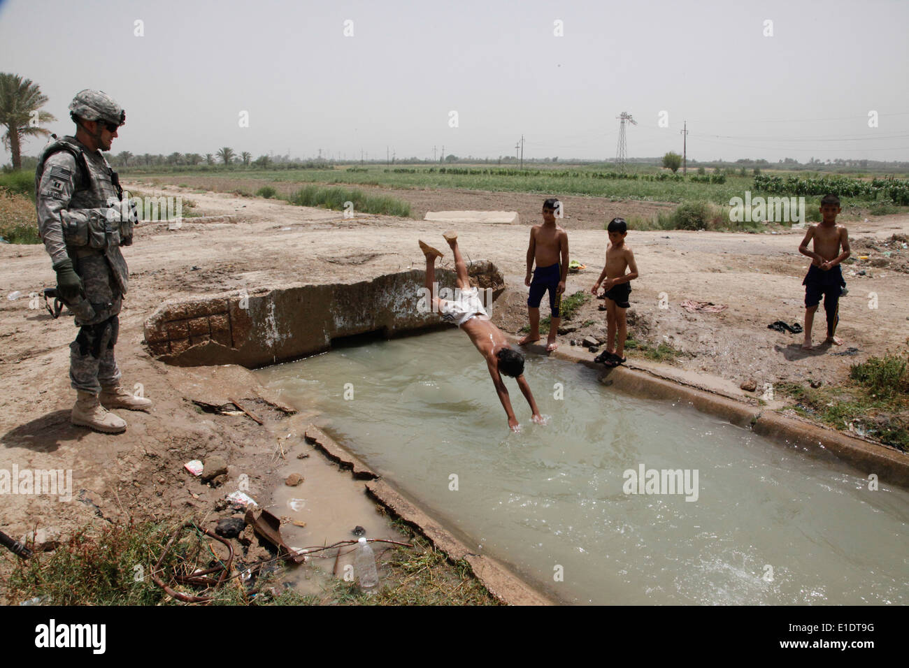 U.S. Army Capt. Andrew Lewis looks on as Iraqi boys play in a canal in Mullah Fayyed, Iraq, June 6, 2010. Lewis, who is command - Stock Image