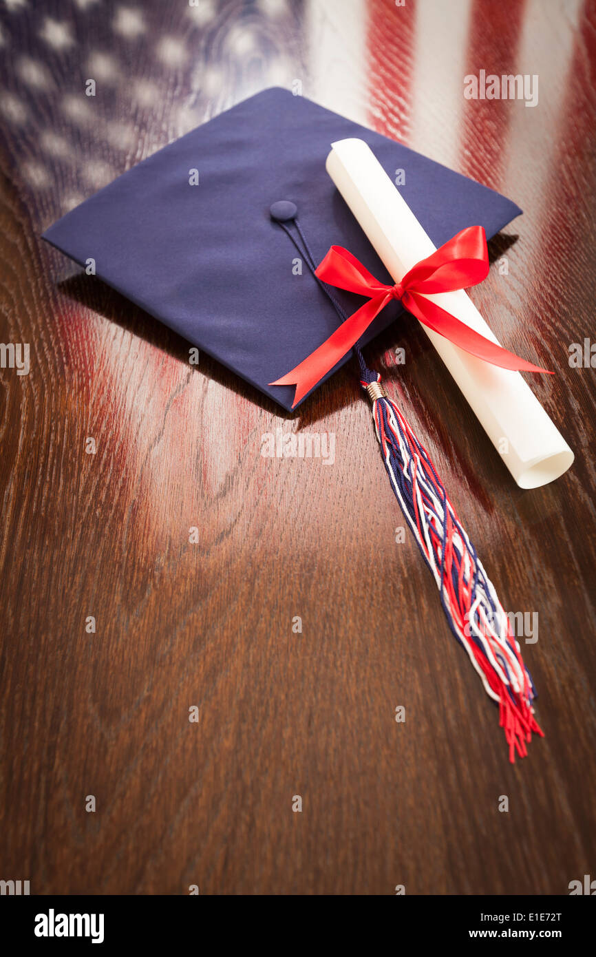 Graduation Cap with Tassel and Dipoma Wresting on Wooden Table with American Flag Reflection. - Stock Image