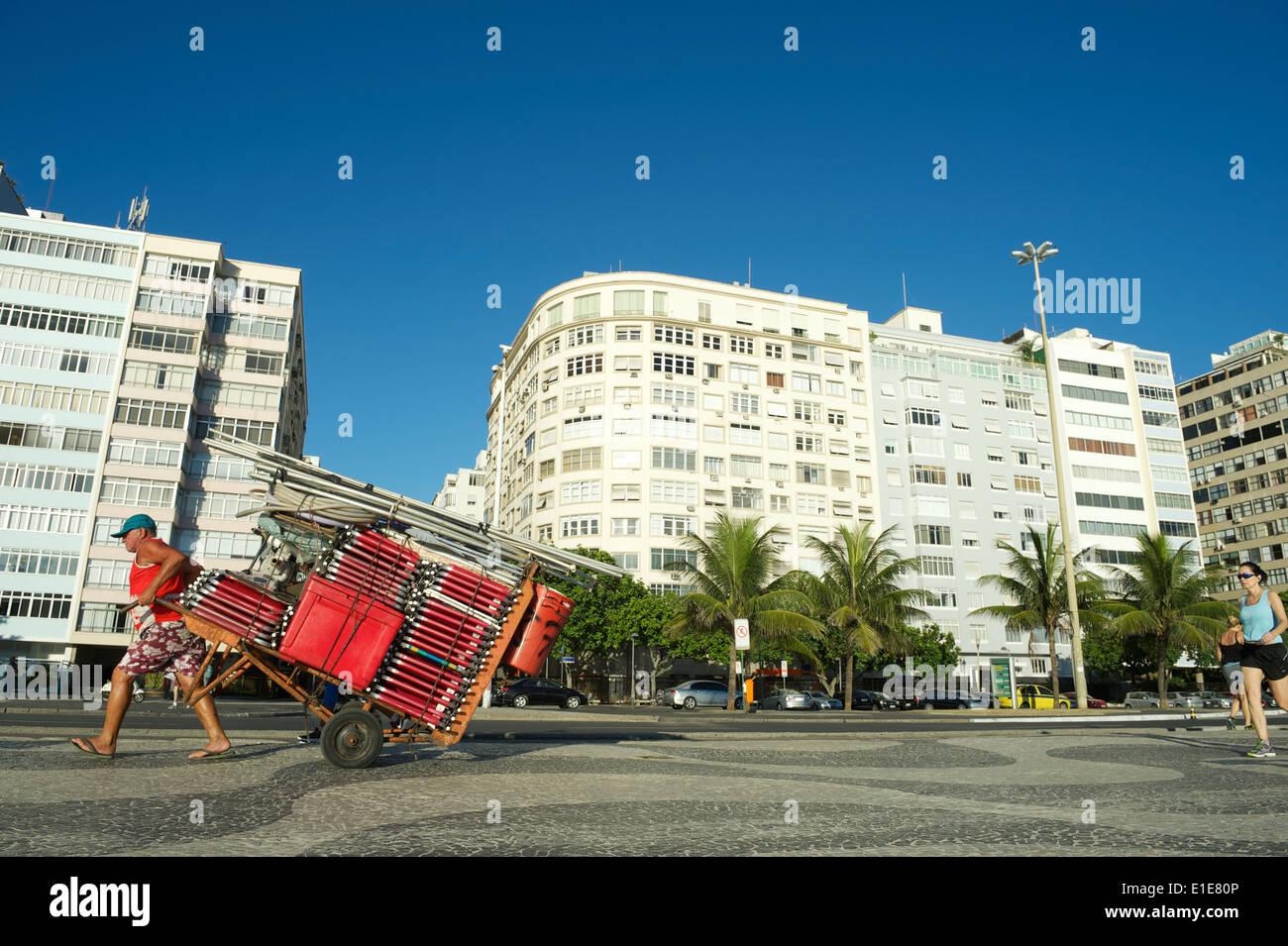 RIO DE JANEIRO, BRAZIL - FEBRUARY 07, 2014: Brazilian man pulls a cart loaded with beach chairs along the Copacabana boardwalk. - Stock Image