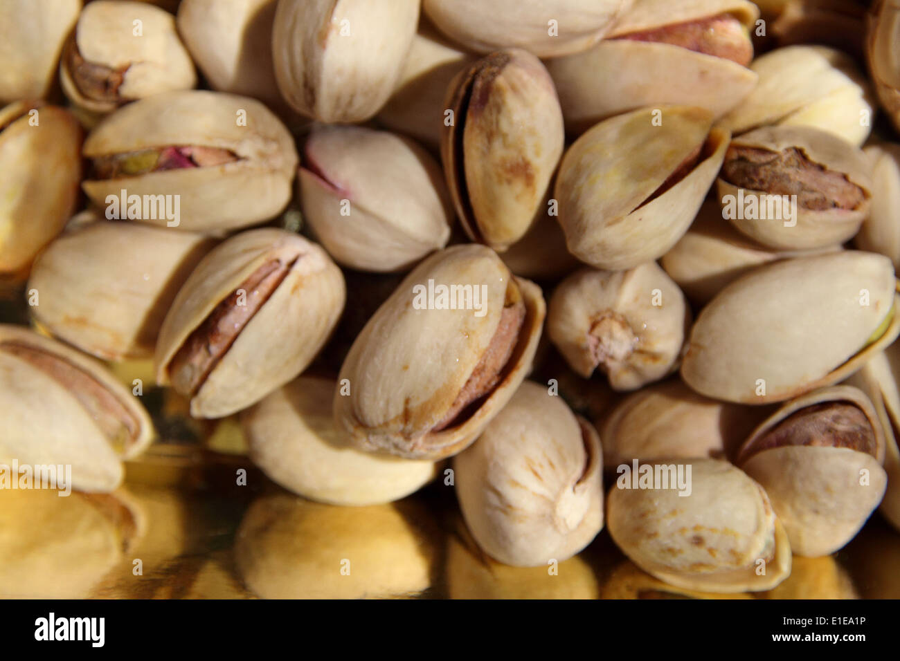 Pale green, edible pistachio nuts enclosed in hard yellow shells are nutritious, rich in vitamins and minerals - Stock Image