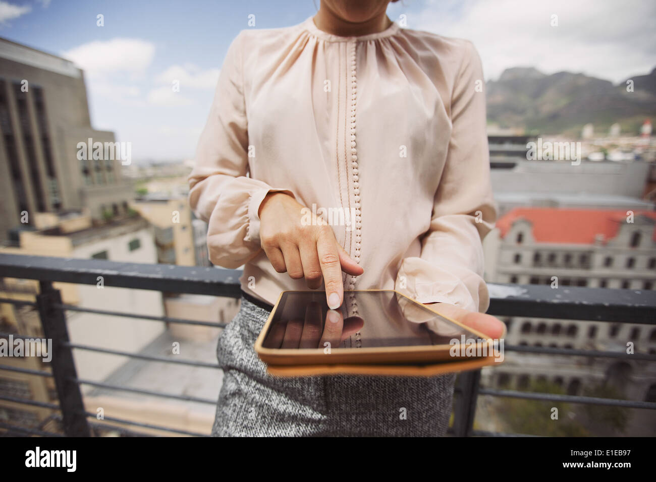 Cropped image of young woman working on tablet PC. Close up image of female standing on balcony using digital tablet. - Stock Image