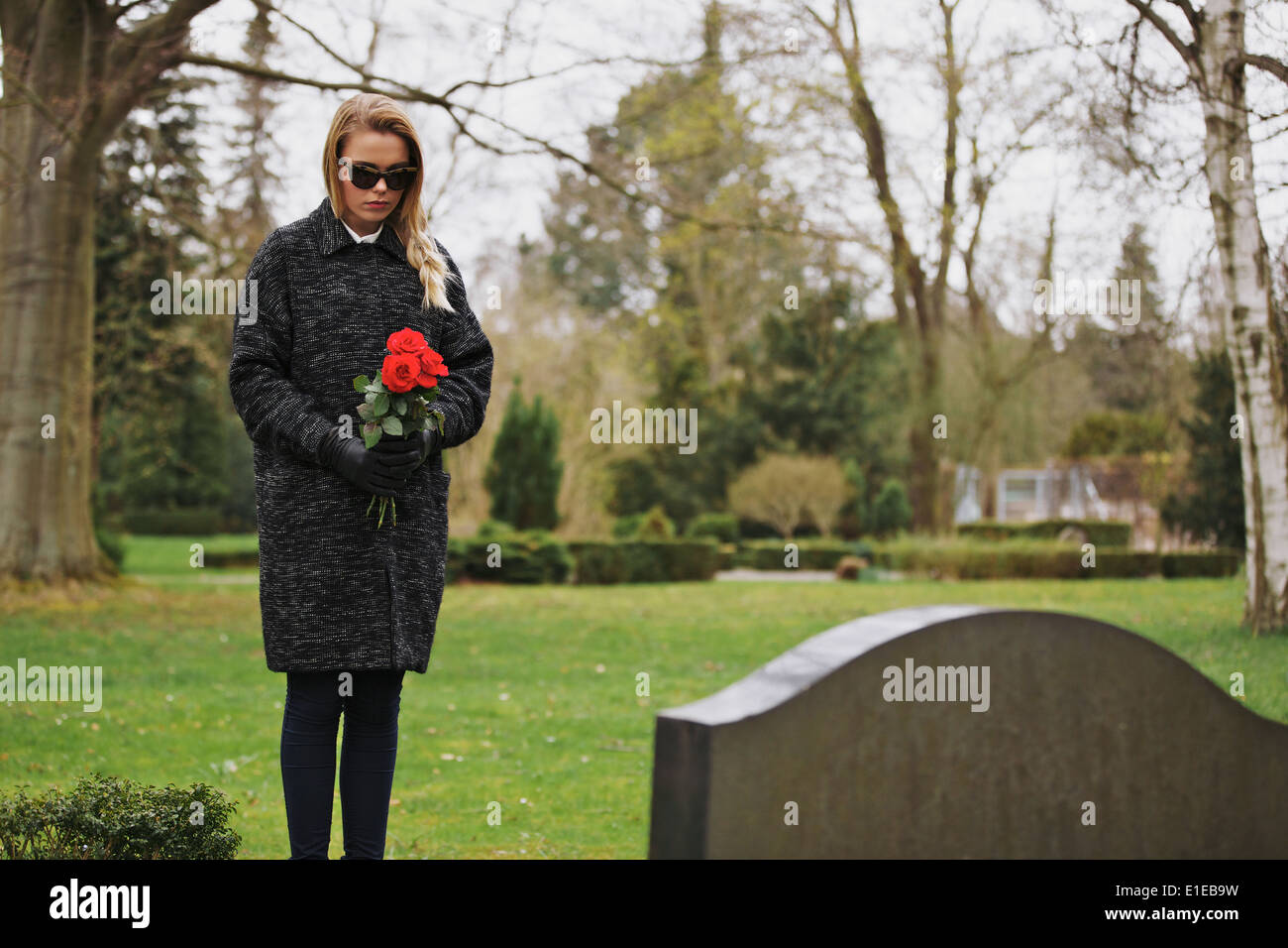Young woman standing at graveside of a deceased family member. Female at cemetery grieving holding flowers. - Stock Image