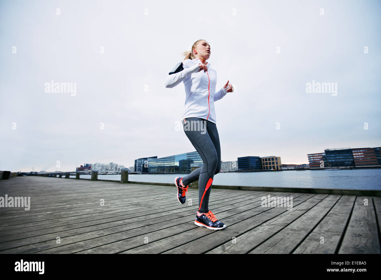 Low angle view of female athlete running along waterfront. Young woman jogging on boardwalk by the river. - Stock Image