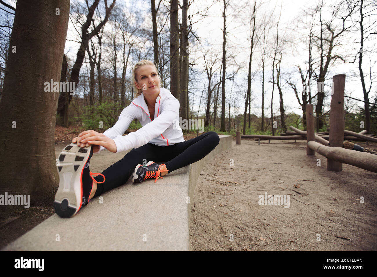 Woman doing stretching exercise in park. Caucasian female model exercising in nature. - Stock Image