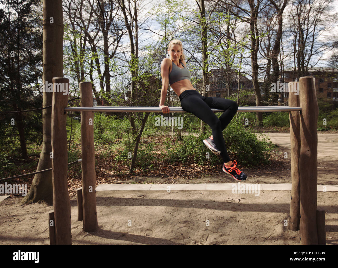 Fit young female sitting on parallel bars. Woman taking rest after triceps dips exercise at park. - Stock Image