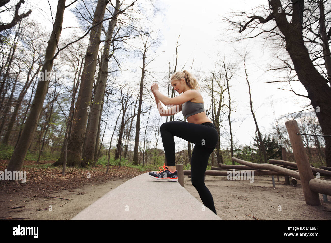 Fitness woman doing stepping up exercise in forest. Caucasian female model working out in nature. - Stock Image