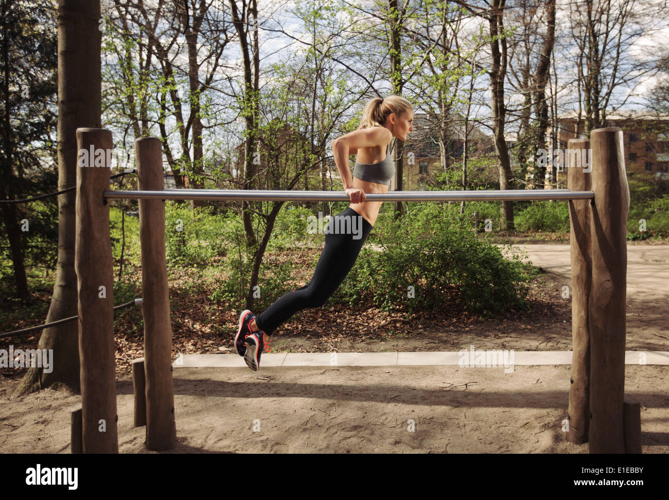 Strong and physically fit young woman doing triceps dips on parallel bars at park. Caucasian fitness female exercising outdoors. - Stock Image