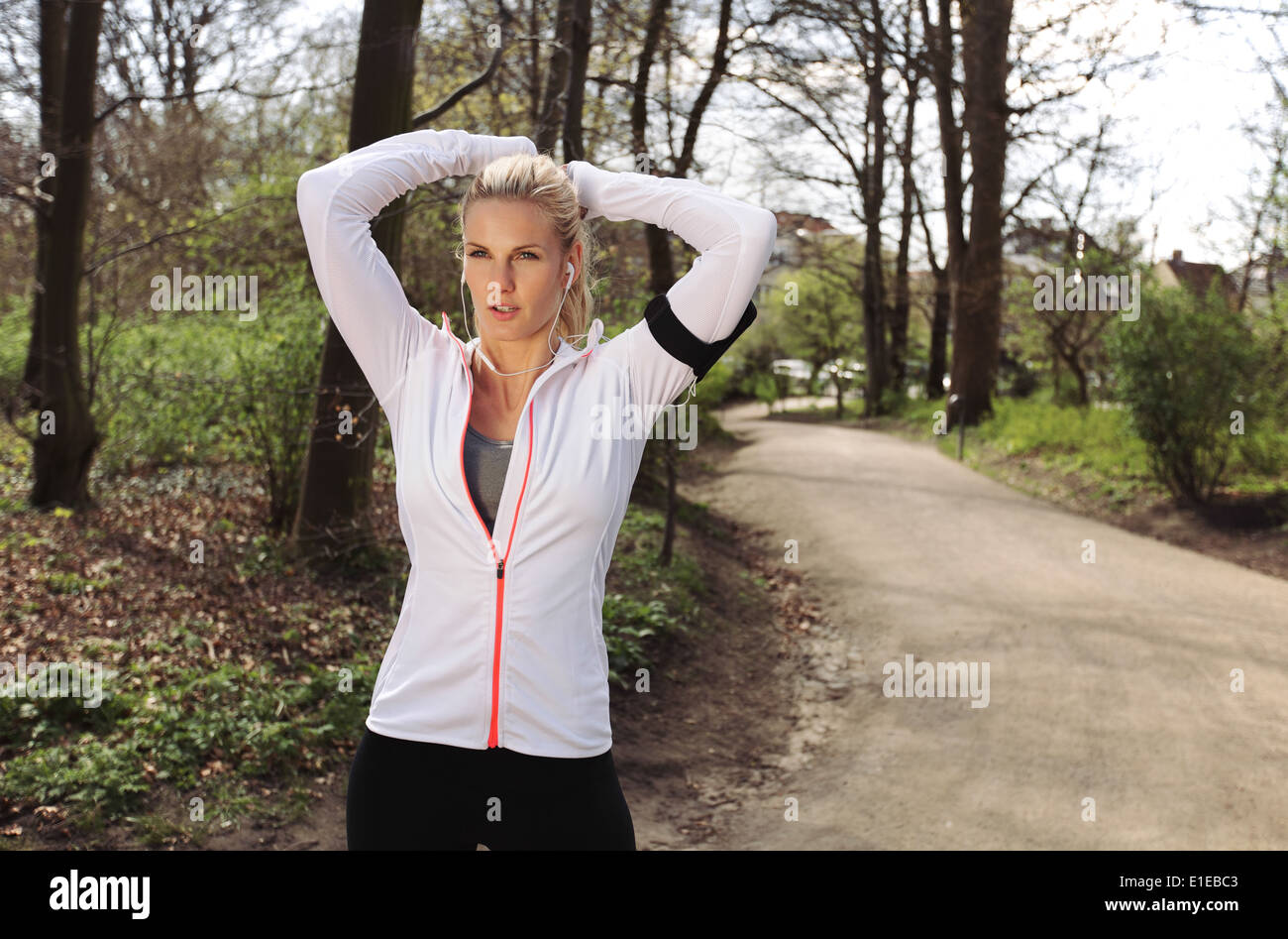 Young fitness woman tying hair before her run. Fit young female athlete focusing on her run in forest. Stock Photo