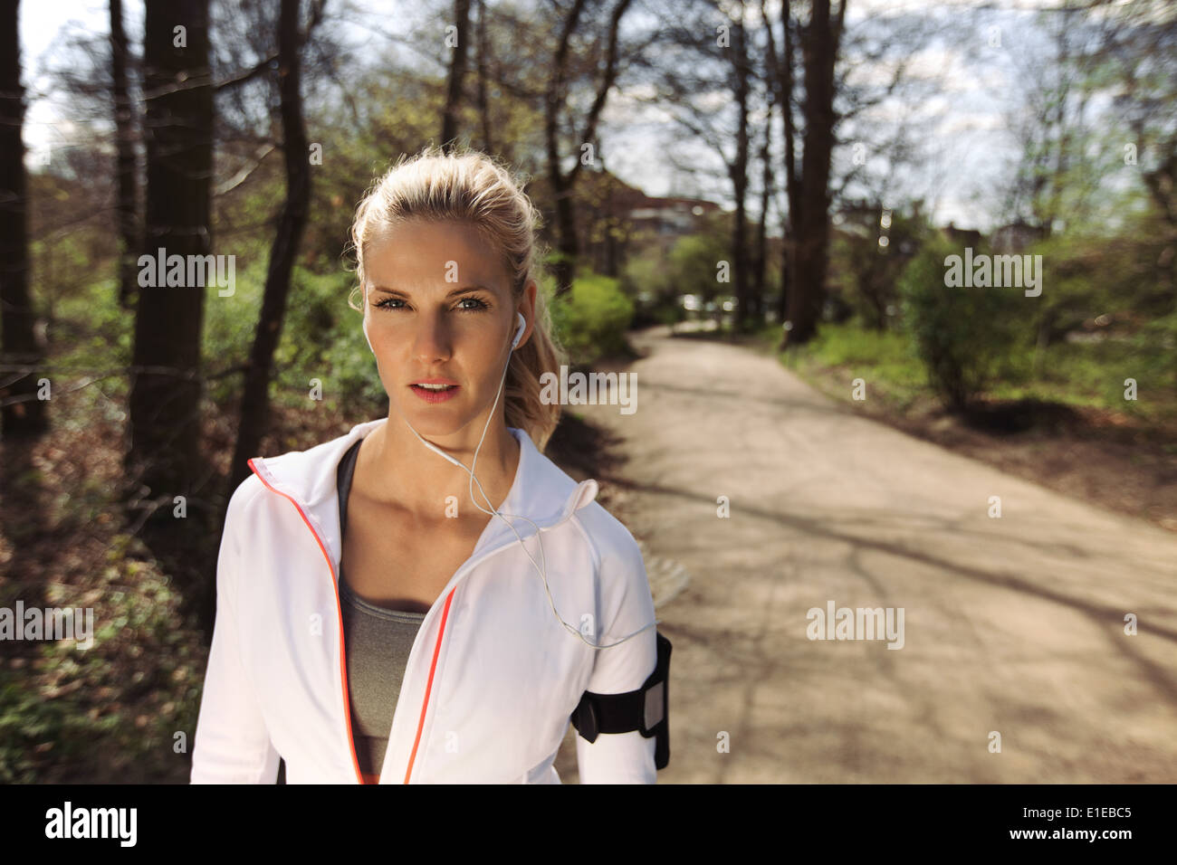 Portrait of pretty young woman in sports clothing wearing earphones while on fitness routine in forest. Young female runner - Stock Image