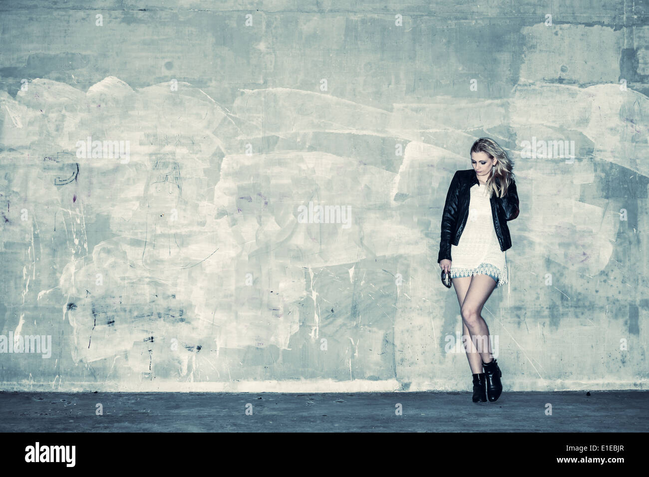 Beautiful urban girl leans against a concrete wall, cross processed image - Stock Image