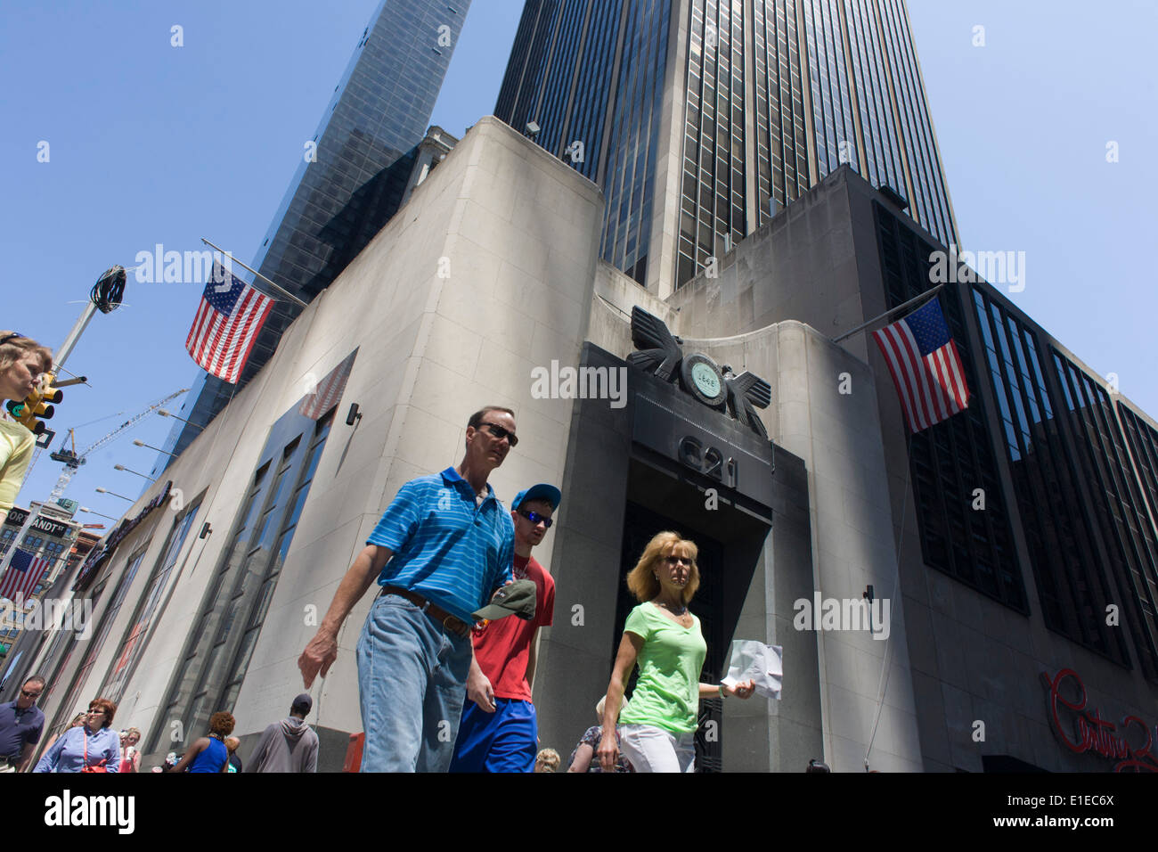 American consumers pass the tall doorway of the East River Savings Bank in Lower Manhattan, New York City. - Stock Image