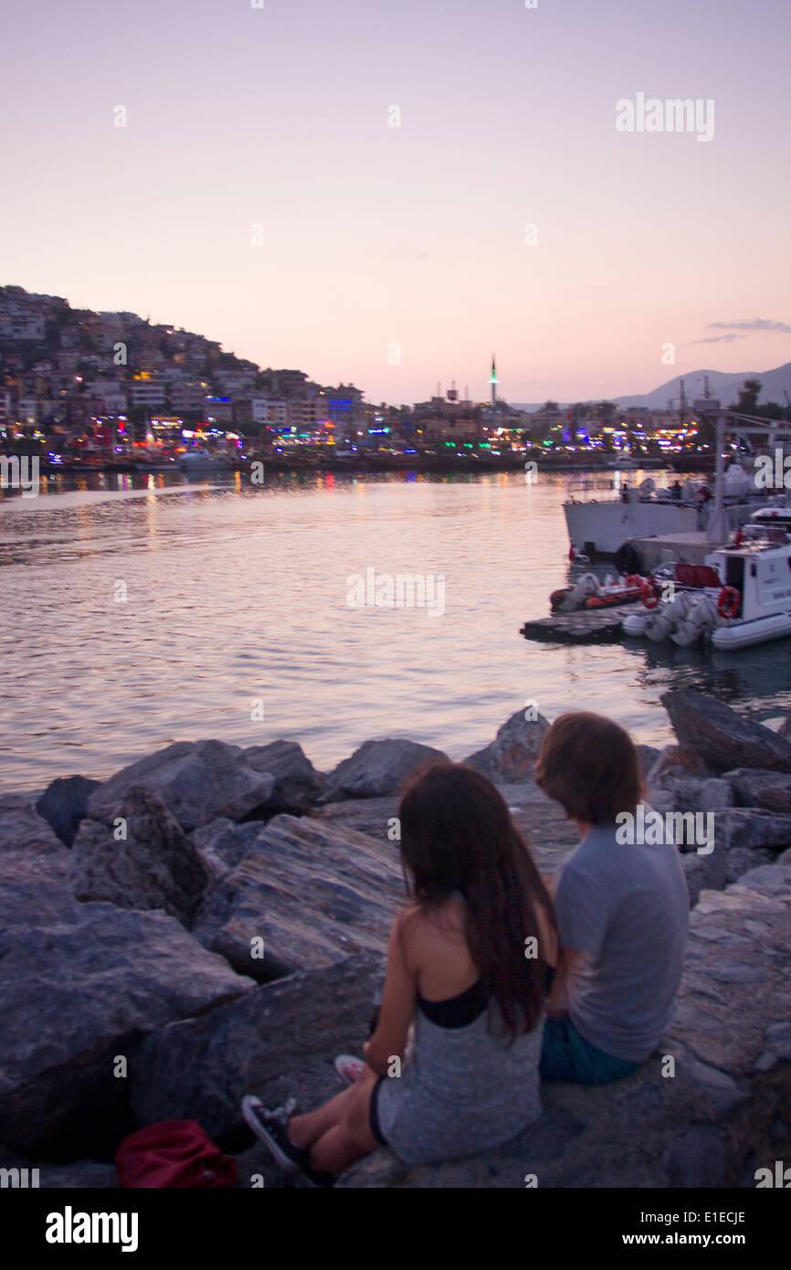 Turkey Alanya Night Sunset Light Sea Mediterranean People View Panorama City Dock Harbour Boat Couple Love Romantic Boy Girl - Stock Image