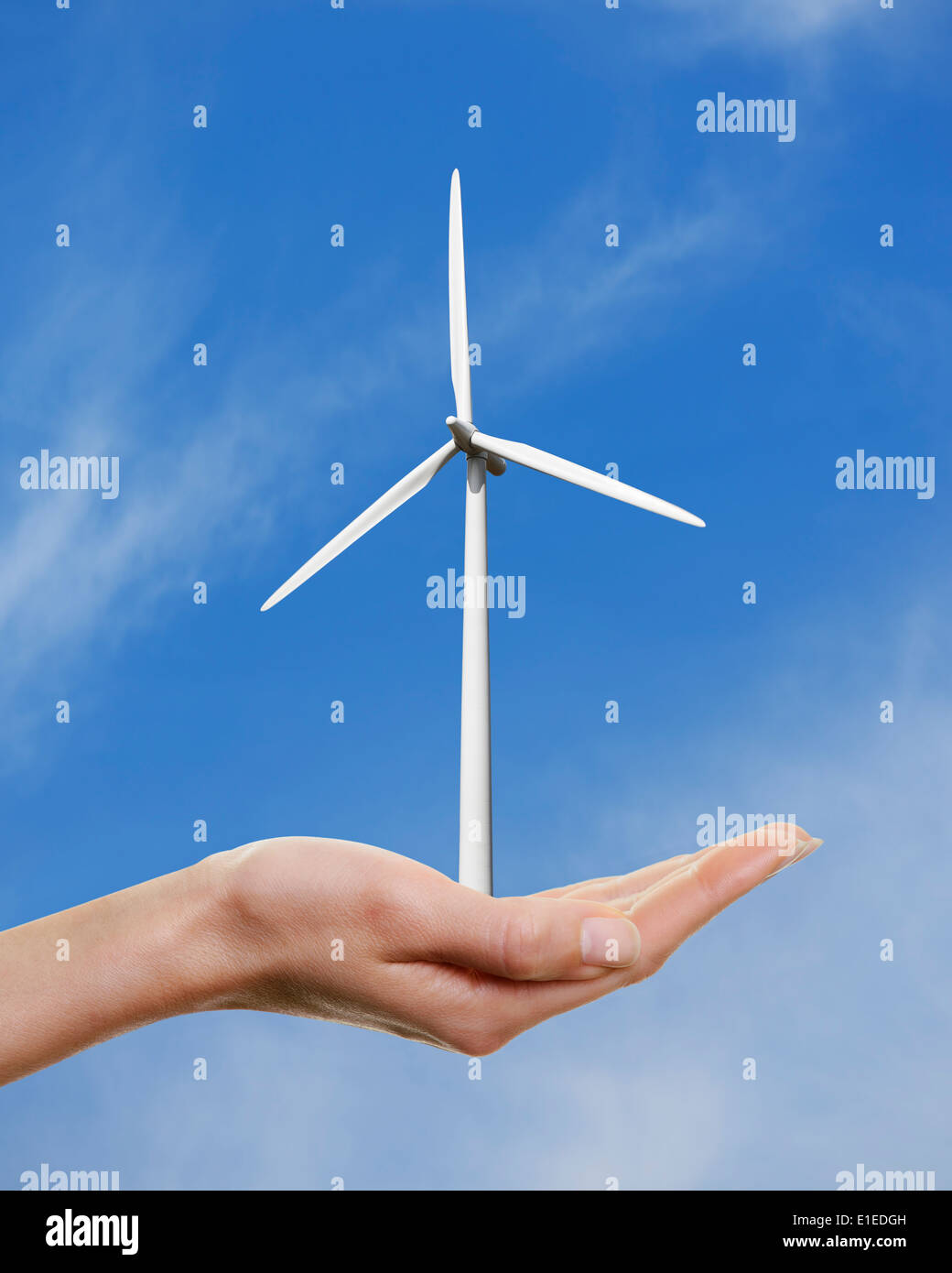 Womans Hand Holding a Wind Turbine against a Blue Sky. - Stock Image