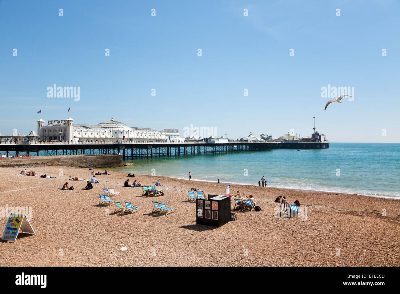 People relaxing at the beach next to the Pier of Brighton, East Sussex, UK - Stock Image