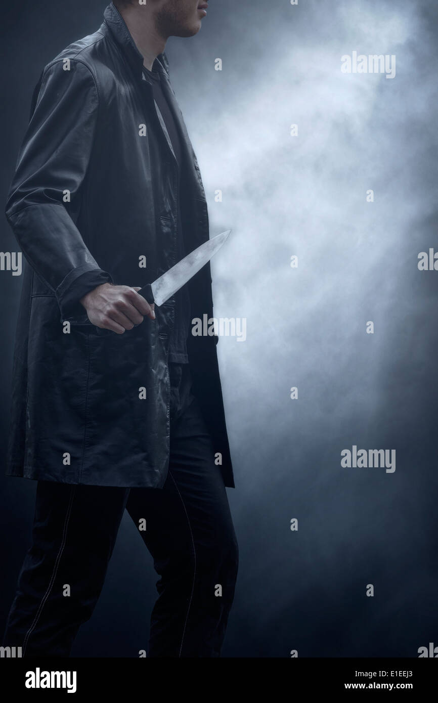 a man in dark clothes with a knife - Stock Image
