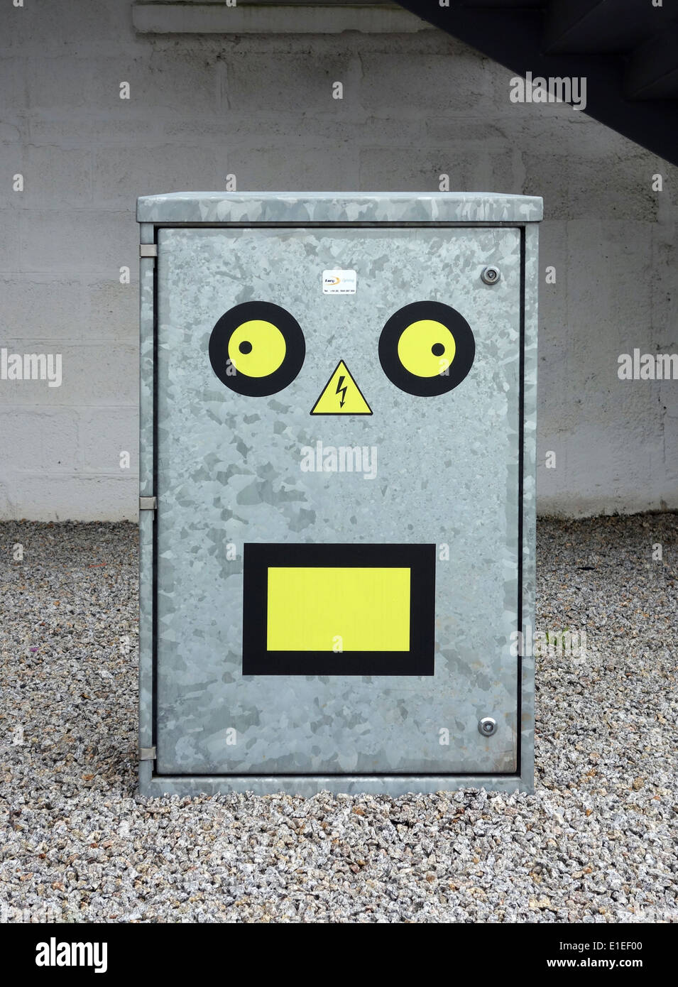 safety labels made into a funny face on an electricity junction box - Stock Image